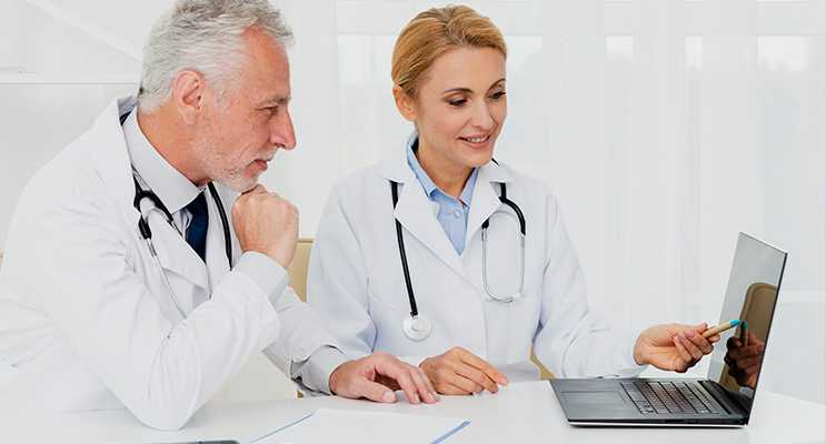 Médicos olhando um laptop